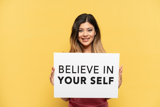 Jong russisch meisje geïsoleerd op gele achtergrond met een plakkaat met tekst believe in your self met gelukkige uitdrukking