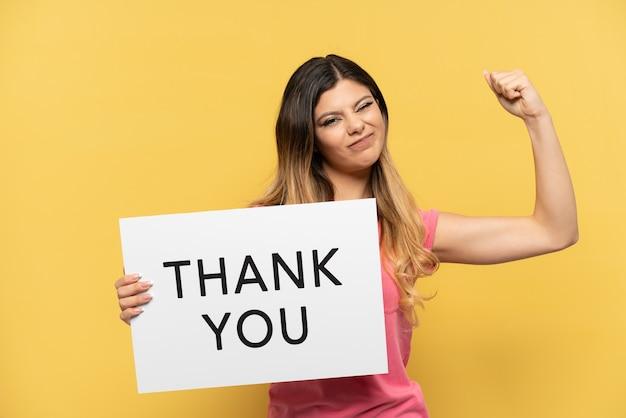 Jong russisch meisje geïsoleerd op gele achtergrond met een plakkaat met tekst dank u en sterk gebaar doen