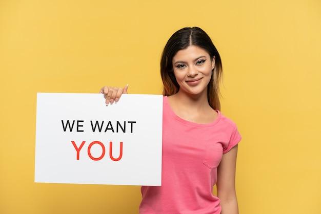 Jong russisch meisje geïsoleerd op gele achtergrond met we want you board met gelukkige uitdrukking
