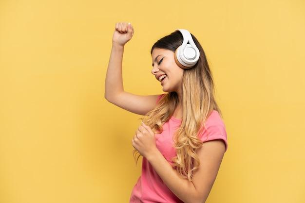 Jong russisch meisje geïsoleerd op gele achtergrond muziek luisteren en dansen