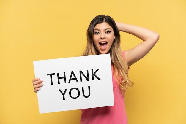 Jong russisch meisje geïsoleerd op gele muur met een bordje met tekst dank u met verbaasde uitdrukking