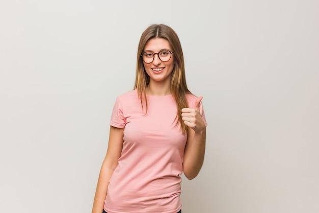 Jong russisch natuurlijk meisje dat en duim glimlacht opheft