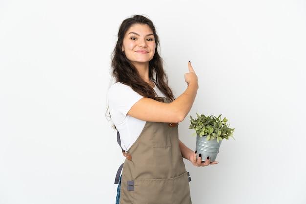 Jong russisch tuinmanmeisje die een geïsoleerde installatie houden die terug richt