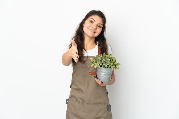 Jong russisch tuinmanmeisje die een installatie houden geïsoleerde handen schudden voor het sluiten van een goede overeenkomst