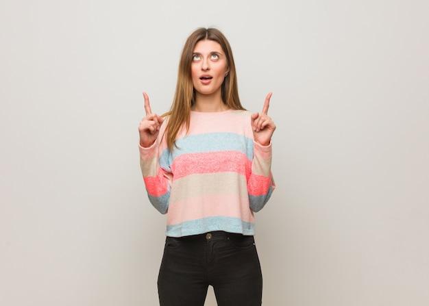 Jong russisch verrast meisje benadrukkend om iets te tonen