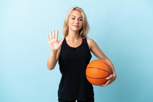 Jong russisch vrouwen speelbasketbal dat op blauwe muur wordt geïsoleerd die vijf met vingers telt