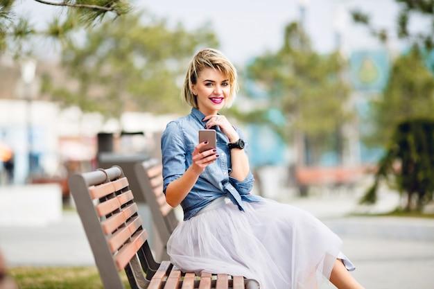 Jong schattig blond meisje met kort haar zittend op een houten bankje met een smartphone en glimlachend gekleed in denim blauw shirt.