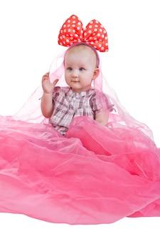 Jong schattig en lief klein meisje (of klein kind) draagt roze jurk met roze en witte polka dot strik zit geïsoleerd op een witte achtergrond