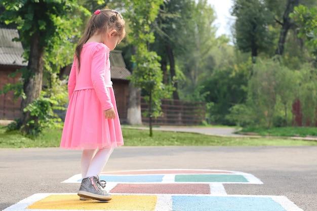 Jong schattig meisje hinkelspel op achtertuin.