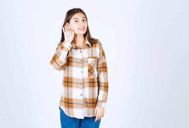 Jong schattig meisje in casual kleding luisteren naar iets op de witte muur.