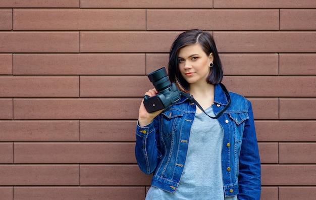 Jong schattig meisje met een blauw denim jasje tegen een bruine bakstenen muur op straat, met een digitale camera in haar handen.