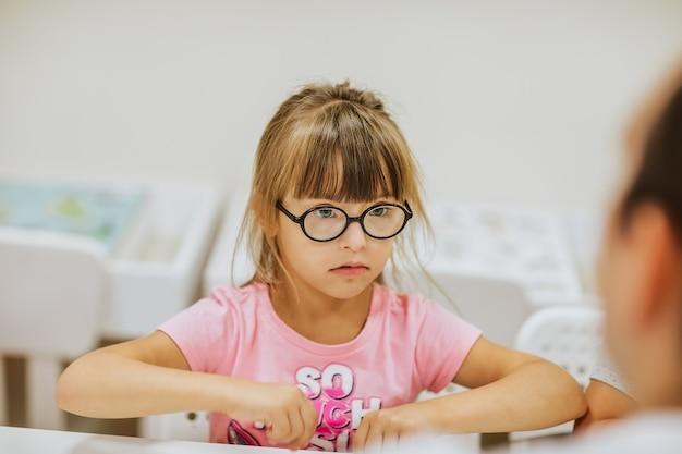 Jong schattig meisje met het syndroom van down in roze shirt en zwarte bril zit aan een wit bureau en kijkt naar haar leraar.
