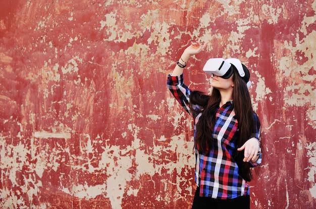 Jong schattig meisje met lang haar in vr-bril in plaidoverhemd op het rode oppervlak van de grungemuur.