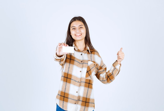 Jong schattig meisje met visitekaartje duimen opgevend op witte muur.