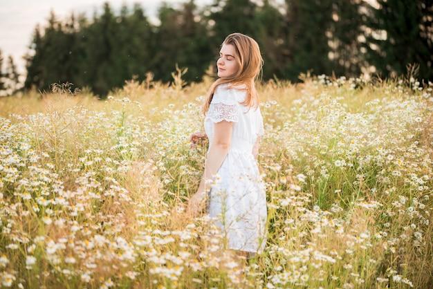 Jong schattig meisje, tedere dromerig verliefd, in een veld met madeliefjes. in jurk en rieten hoed. hete zonnige zomer, zonsondergang in het dorp. vrijheid concept en levensstijl