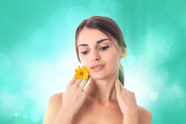 Jong schattig meisje zorgt voor haar huid met gele bloem in handen geïsoleerd op een witte achtergrond. gezondheidszorgconcept. lichaamsverzorgingsconcept. jonge vrouw met een gezonde huid.