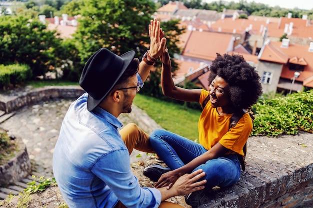 Jong schattig multiraciaal koppel zittend op de muur van de vesting, hand in hand en high five geven aan elkaar.