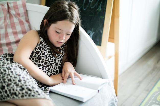 Jong schoolmeisje dat een boek in de ruimte thuis leest.