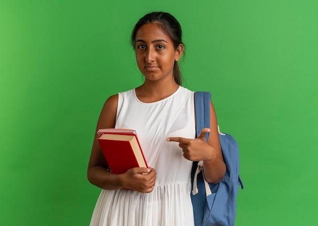 Jong schoolmeisje draagt rugzak bedrijf en wijst op boek met notebook