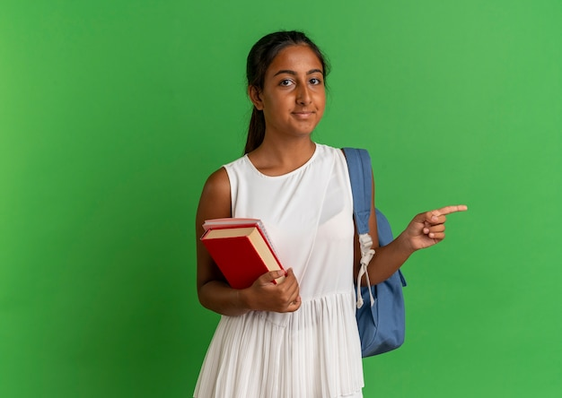 Jong schoolmeisje draagt rugzak bedrijf notebook met boek en punten aan de zijkant