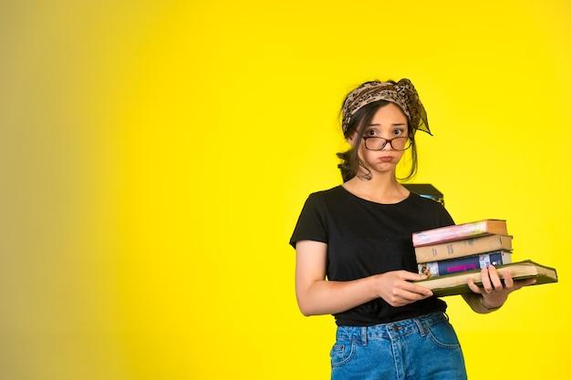 Jong schoolmeisje in bril houdt haar boeken vast en voelt zich moe.