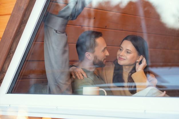 Jong sereen aanhankelijk stel dat in het winterweekend bij het grote raam van het landhuis zit, elkaar aankijkt en met elkaar communiceert