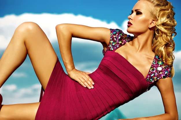 Jong sexy blond vrouwenmodel in avond het rode kleding stellen op blauwe hemelachtergrond