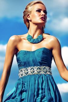 Jong sexy blond vrouwenmodel in avondjurk het stellen op blauwe hemelachtergrond