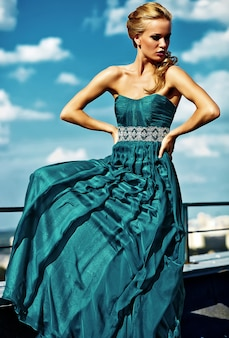 Jong sexy blond vrouwenmodel in avondjurk het stellen op blauwe hemelmuur