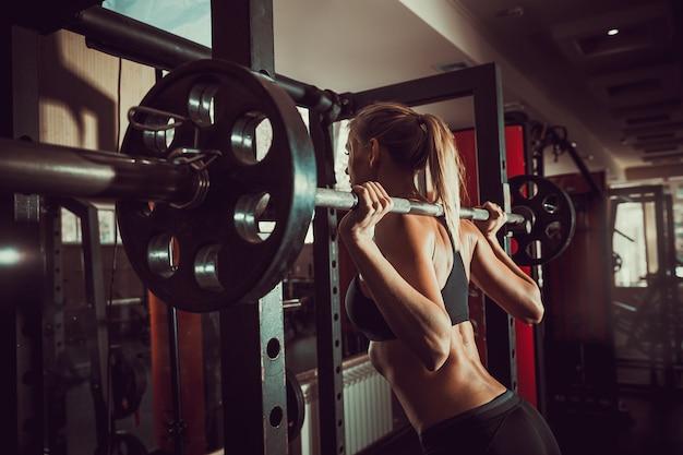 Jong sexy blondemeisje in de gymnastiek die hurkzit voorbereidingen treffen te doen