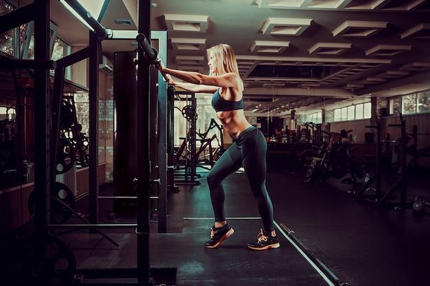 Jong sexy blondemeisje in de gymnastiek die oefening voorbereidingen treffen te doen