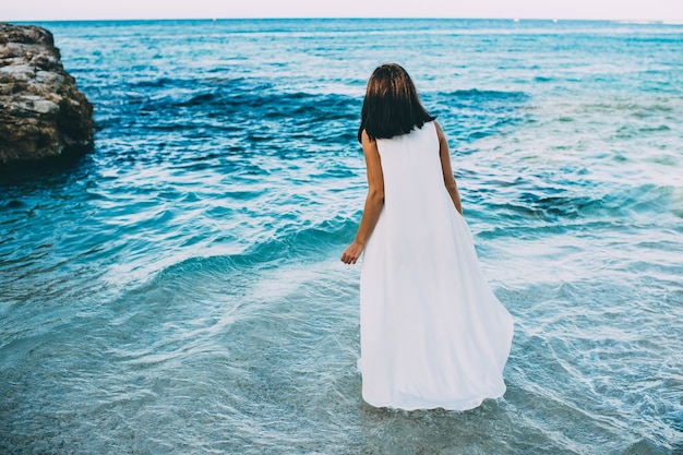 Jong sexy brunette in blauw water in een witte kleding op het strand in griekenland