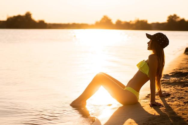 Jong sexy meisje bij zonsondergang op het strand