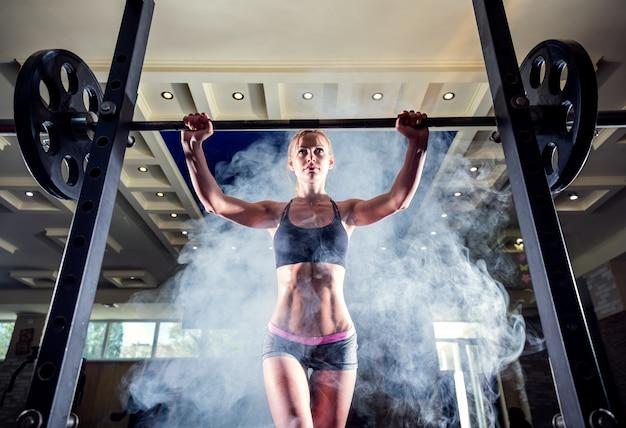 Jong sexy meisje in de gymnastiek die hurkend op rookachtergrond voorbereidingen treffen te doen