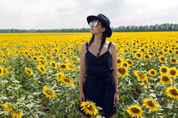 Jong sexy meisje in zwarte jurk en hoed in veld met gele zonnebloemen