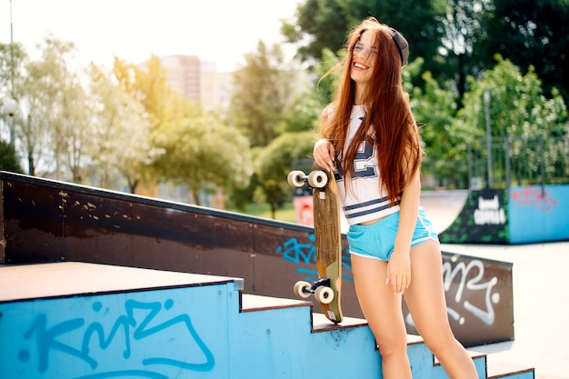 Jong sexy mooi slank meisje met een skateboard in de stad. modieus meisje hipster in een pet en zonnebril.