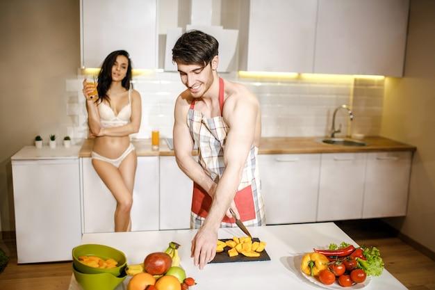 Jong sexy paar na intimiteit in keuken in nacht. knappe, voorzichtige man die voedsel op bureau snijdt. mooi heet model staan op rug in witte lingerie. ze houdt een glas sap in haar handen en glimlacht.