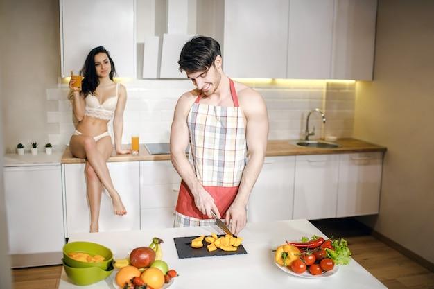 Jong sexy paar na intimiteit in keuken in nacht. voorzichtige goedgebouwde man draagt een schort en snijdt fruit op het bureau. mooie hete vrouw zitten op tafel met gekruiste benen en kijken naar man.