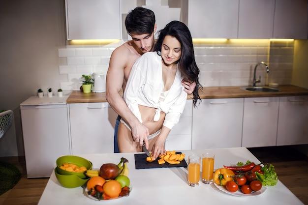 Jong sexy paar na intimiteit in keuken in nacht