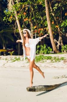 Jong sexy slank meisje dat zich op één been op een stuk hout op een strand bevindt dat witte bikinizwemkleding draagt. ze draagt een wit overhemd, een donkere zonnebril en een strooien hoed. ze is gebruind en stijlvol