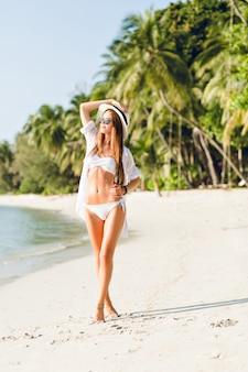 Jong sexy slank meisje dat zich op een strand bevindt dat witte bikinibadmode draagt. ze draagt een wit overhemd, een donkere zonnebril en een strooien hoed. ze is gebruind en stijlvol.