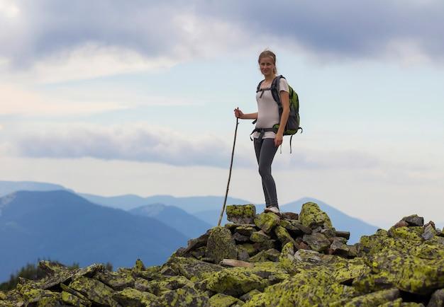 Jong slank blond toeristenmeisje met rugzak en stok die zich op rotsachtige bovenkant tegen heldere blauwe ochtendhemel bevinden op de mistige achtergrond van het bergketenpanorama. toerisme, reizen en klimmen concept.