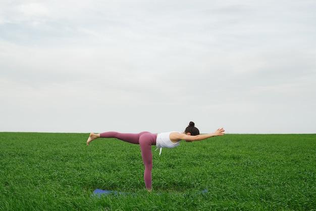 Jong slank meisje doet yoga buiten in een groen veld
