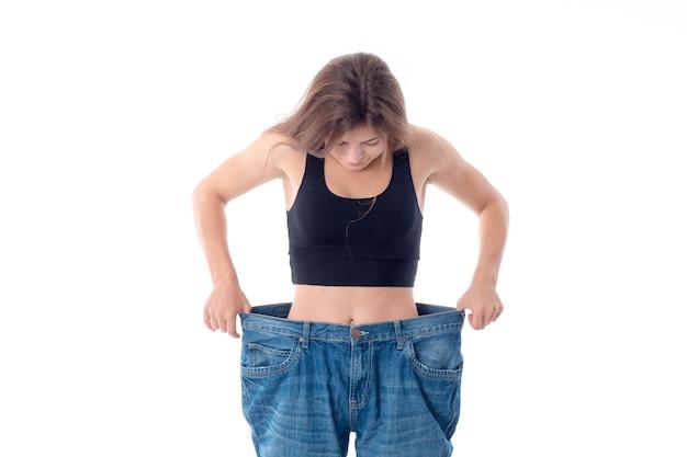 Jong slank meisje neemt grote wijde jeans geïsoleerd op een witte achtergrond
