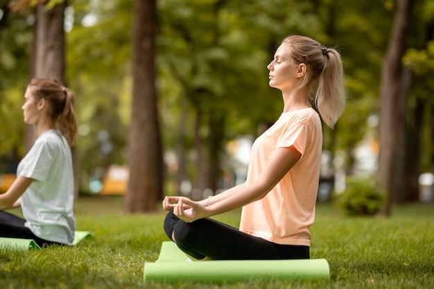 Jong slank meisje zit in de lotuspositie met gesloten ogen en doet oefeningen met andere meisjes op groen gras in het park op een warme dag. .