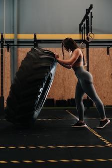Jong spaans meisje met sterke spieren die een wiel opheffen in een crossfit-gymnasium