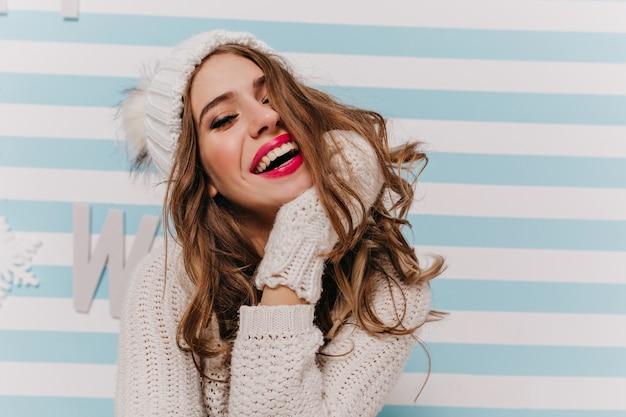 Jong, speels, vrolijk meisje in gebreide outfit uitdagend lachend en poseren, direct kijkend