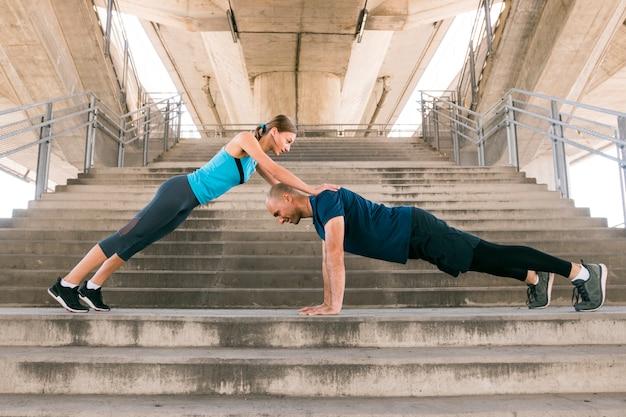 Jong sportenpaar die op de trap uitoefenen