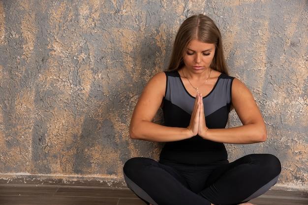 Jong sportief meisje dat meditatie doet.