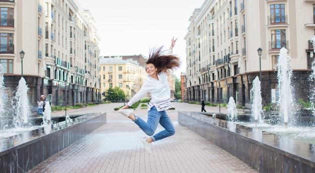 Jong sportief meisje dat voor vreugde bij de fontein springt.